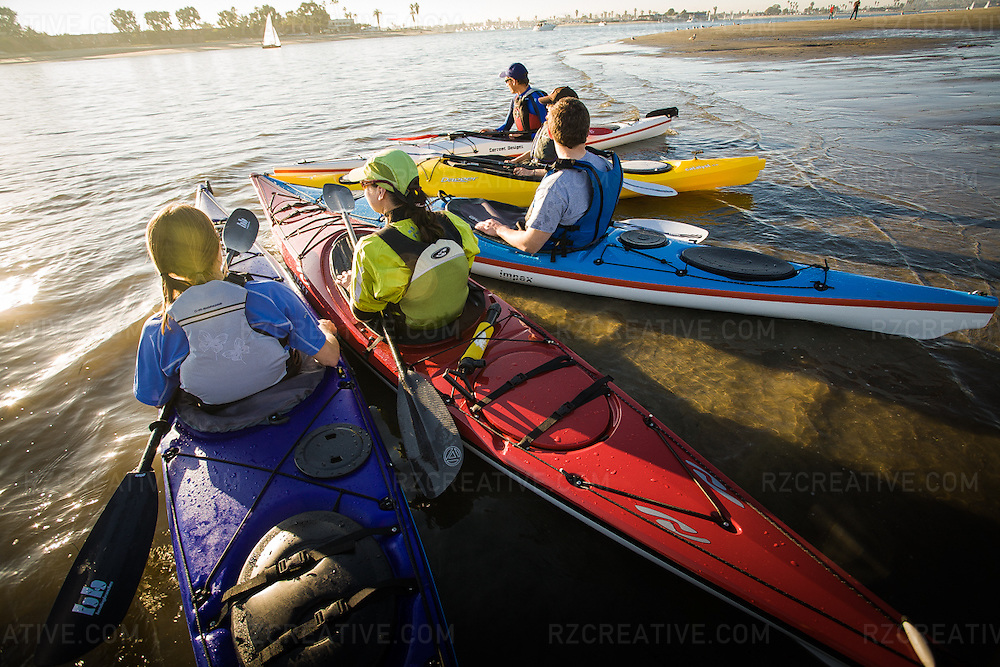 A group of sea kayakers face into the sun in Mission Bay, San Diego, California.