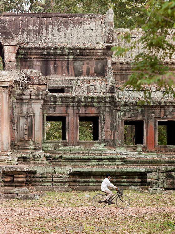 A local man cycles through the forest, past an old temple near Angkor Wat at Angkor, Siem Reap Province, Cambodia