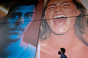 A man wearing a face covering walks beneath a large billboard featuring an ecstatic young woman, on the exterior of a soon-to-open fitness club opposite Liverpool Station in the City of London, the capitals financial district, on 24th February 2021, in London, England.