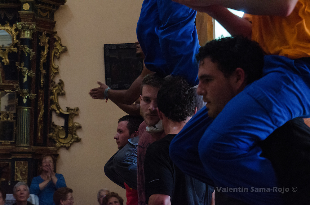 Faces of the men holding another person with their chins while performing a human tower during the rehearsal of Cetina's Contradanza in 'San Juan Lorenzo' hermitage.