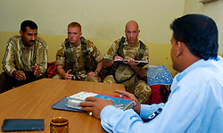 British soldiers from the Duke of Wellington's Regiment wearing desert camouflage, and body armor, carrying SA80 assault rifles which are fitted with SUSAT sights, pay a visit to an Iraqi Police Station in the Basra area during Op-Telic in March 2005.