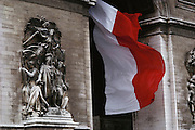 Arc de Triumph close-up with billowing French flag. Paris, France.