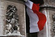 Arc de Triumph close-up with billowing French flag. Paris, France.