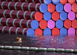 © Licensed to London News Pictures. 18/06/2018. London, UK. A swimmer passes close to artist Christo's latest work 'The Mastaba' unveiled on The Serpentine in Hyde Park today. The 20m high installation, made up of 7,506 horizontally stacked barrels, is 30m wide and 40m long. Photo credit: Peter Macdiarmid/LNP