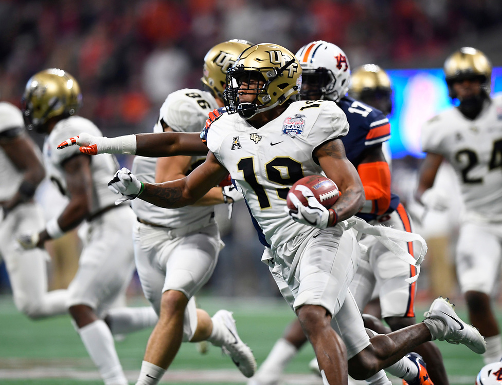 UCF Knights kick returner Mike Hughes (19) runs during the second half of the Chick-fil-A Peach Bowl NCAA college football game at the Mercedes-Benz Stadium in Atlanta, January 1, 2018. UCF won 34-27 to go undefeated for the season. (David Tulis via Abell Images for Chick-fil-A Peach Bowl)