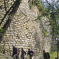 Travelers explore below fortress walls at Kuelap, a stronghold of the pre-Incan Chachapoyan culture.