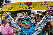 07 AUGUST 2013 - BANGKOK, THAILAND: A Thai Yellow Shirt protester holds up a banner supporting the King of Thailand during an anti-government protest in Lumpini Park in Bangkok. About 2,500 protestors opposed to an amnesty bill proposed by Thailand's ruling party marched towards the Thai parliament in the morning. The amnesty could allow exiled fugitive former Prime Minister Thaksin Shinawatra to return to Thailand. Thaksin's supporters are in favor of the bill but Thai Yellow Shirts and government opponents are against the bill. Thai police deployed about more than 10,000 riot police and closed roads around the parliament. Although protest leaders called off the protest rather than confront police, a few people were arrested for assaulting police when they tried to break through police lines. Several police officers left the scene under medical care after they collapsed in the heat.    PHOTO BY JACK KURTZ
