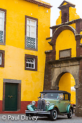 A classic car sits within the walls of an old fort, now a restaurant, in Funchal, Madeira. MADEIRA, September 25 2018. © Paul Davey