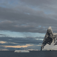"""Mountains called """"Una's Teats"""" tower above the Lemaire Channel, a popular cruise ship destination in Antarctica that is sometimes called """"Kodak Gap."""""""