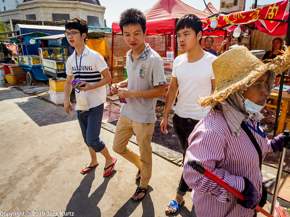 """15 FEBRUARY 2019 - SIHANOUKVILLE, CAMBODIA:  Chinese casino workers in the Nanhai Pearl Hotel Apartment watch a Cambodian woman who works as a street sweeper in Sihanoukville. There are about 80 Chinese casinos and resort hotels open in Sihanoukville and dozens more under construction. The casinos are changing the city, once a sleepy port on Southeast Asia's """"backpacker trail"""" into a booming city. The change is coming with a cost though. Many Cambodian residents of Sihanoukville  have lost their homes to make way for the casinos and the jobs are going to Chinese workers, brought in to build casinos and work in the casinos.      PHOTO BY JACK KURTZ"""