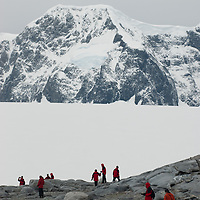 Tourists explore a hillside near Damoy Point on Wiencke Island, Antarctica. Behind are peaks of The Seven Sisters of Fief in the Fief Mountains.