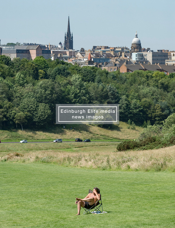 A solo sun worshipper in Holyrood Park on what is predicted to be the hottest day of the year.<br /> <br /> © Dave Johnston / EEm