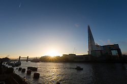 © Licensed to London News Pictures. 22/12/2016. LONDON, UK.  Sunrise on the River Thames behind Toewr Bridge and the London Shard after early fog lifted this morning. After a cold and foggy start to the day, London is now seeing bright and sunny weather today. Photo credit: Vickie Flores/LNP