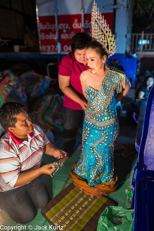 19 JANUARY 2014 - BANGKOK, THAILAND:  A performer in a mor lam show gets help getting into her costume before going on stage at a mor lam show in Khlong Tan Market in Bangkok. Mor Lam is a traditional Lao form of song in Laos and Isan (northeast Thailand). It is sometimes compared to American country music, song usually revolve around unrequited love, mor lam and the complexities of rural life. Mor Lam shows are an important part of festivals and fairs in rural Thailand. Mor lam has become very popular in Isan migrant communities in Bangkok. Once performed by bands and singers, live performances are now spectacles, involving several singers, a dance troupe and comedians. The dancers (or hang khreuang) in particular often wear fancy costumes, and singers go through several costume changes in the course of a performance. Prathom Bunteung Silp is one of the best known Mor Lam troupes in Thailand with more than 250 performers and a total crew of almost 300 people. The troupe has been performing for more 55 years. It forms every August and performs through June then breaks for the rainy season.              PHOTO BY JACK KURTZ