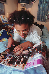Young woman with Cerebral Palsy lying on bed in residential care centre reading magazine,