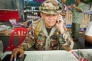 """May 12 - BANGKOK, THAILAND: Maj. Gen. KHATTIYA """"Seh Daeng"""" SAWASDIPOL uses a cell phone and computer to stay in touch with Red Shirt barricades in the Red Shirt camp in Bangkok Wednesday. Seh Daeng, as he is known, has emerged as the Red Shirts unofficial military commander. He has organized the barricades that ring the Red Shirt camp and has threatened to organize a guerilla campaign against the government if the Red Shirt protest is crushed by force. Seh Daeng is a hero to many Thais because he is credited with crushing Thailand's communist insurgency in the 1970's and 80's. He was the commander of Thailand's Internal Security Operations Command but after his political activities became apparent he was made the head aerobics instructor for the Thai army. He is now seen as one of the major personalities destabilizing the country and the government alleges that he is behind many of the grenade attacks and drive by shootings directed at government buildings and officials and he is wanted for a long list of felony offenses including weapons charges and terrorism related charges. Although some Red Shirts have officially repudiated him, he is still frequently seen around the Reds' barricades. The army has started proceedings to fire him, but he remains a general on active duty.   Photo by Jack Kurtz"""