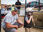 14 AUGUST 2019 - DES MOINES, IOWA:  A man helps his son get ready for Mutton Busting at the Iowa State Fair. The Iowa State Fair is one of the largest state fairs in the U.S. More than one million people usually visit the fair during its ten day run. The 2019 fair run from August 8 to 18.                PHOTO BY JACK KURTZ