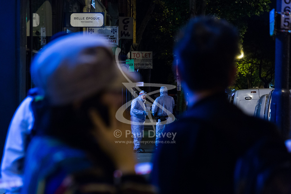 Local residents who are unable to return to their homes within the large cordon look on as forensics investigators work at the scene following a fatal stabbing of a man in broad daylight at around 6.30pm on Upper Street in Islington, North London. London, May 21 2018.