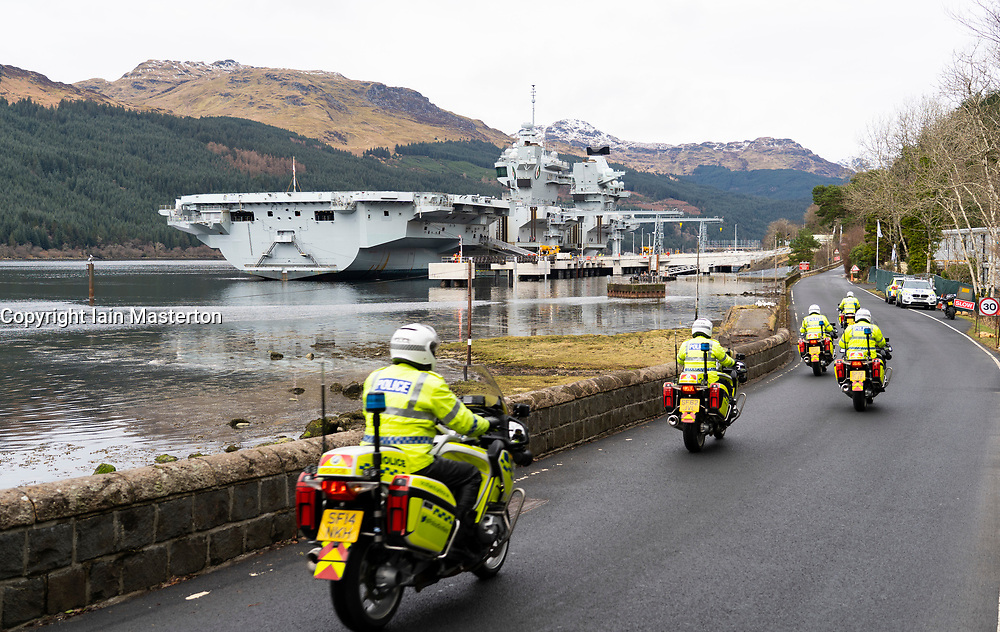 Finnart, Scotland, UK. 15 March 2021. Royal Navy aircraft carrier HMS Queen Elizabeth berthed on Long Loch  at Glenmallon to take on supplies and munitions ahead of naval exercises part of UK Carrier Strike Group 2021. Pic; Heavy police security surrounded the warship.  Iain Masterton/Alamy Live News