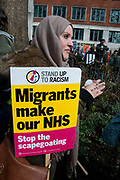 Tens of thousands of health workers, activists and members of the public protested against austerity and cuts in the NHS National Health Service on March 4th 2017 in London, United Kingdom. A woman wearing a headscarf has a placard which says Migrants make our NHS. Stop the scapegoating. On her finger she has written Hashtag our NHS.