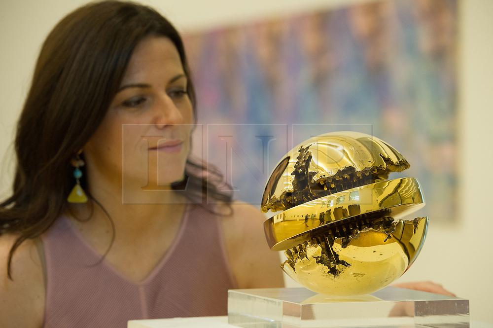 © London News Pictures. 26/06/15. London, UK. A Bonham's employee looks at Arnaldo Pomodoro's 1968 'Rotante', which is part of Bonhams Contemporary Art Sale, New Bond Street, Central London. Photo credit: Laura Lean/LNP