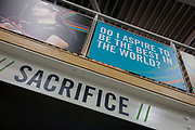 Motivational sports psychology in the gym at the Sports Institute, University of Ulster, Northern Ireland. The word sacrifice appears on a high gantry in the gym. From the chapter entitled 'The Law of Gravity' and from the book 'Risk Wise: Nine Everyday Adventures' by Polly Morland (Allianz, The School of Life, Profile Books, 2015).