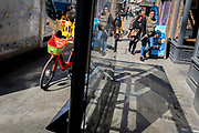 A discarded Lime rental bike stands in a bus shelter as Londoners pass-by during the third lockdown of the Coronavirus pandemic, on 29th March 2021, in London, England.