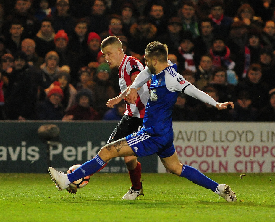 Lincoln City's Terry Hawkridge vies for possession with Ipswich Town's Luke Chambers<br /> <br /> Photographer Andrew Vaughan/CameraSport<br /> <br /> Emirates FA Cup Third Round Replay - Lincoln City v Ipswich Town - Tuesday 17th January 2017 - Sincil Bank - Lincoln<br />  <br /> World Copyright © 2017 CameraSport. All rights reserved. 43 Linden Ave. Countesthorpe. Leicester. England. LE8 5PG - Tel: +44 (0) 116 277 4147 - admin@camerasport.com - www.camerasport.com