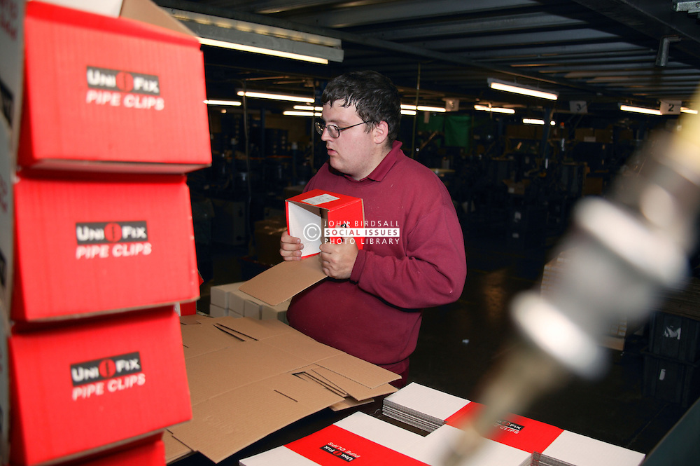 Man with learning disability working in factory assembling cardboard boxes,