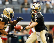 New Orleans Saints quarterback Drew Brees (9) hands the ball to New Orleans Saints running back Mark Ingram (28) against the Dallas Cowboys at Cowboys Stadium in Arlington, Texas, on December 23, 2012.  (Stan Olszewski/The Dallas Morning News)
