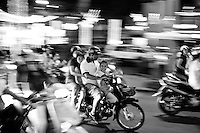 Family of three riding a motorbike in the blur of Saigon traffic at night.