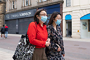 Two women wearing matching surgical blue face masks to prevent the spread of Covid-19 as they walk down the high street on 8th August, 2021 in Leeds, United Kingdom. The British Department of Health has announced that as of Monday, new guidance will mean that even the fully vaccinated will be advised to wear a mask and limit their contact with others if they come into contact with somebody who tests positive for Coronavirus.