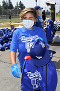 Netflix actress Annie Gonzalez loads care packages into a car at the Dodger Day Drive-Thru at Belvedere Park, Tuesday, June 30, 2020, in Los Angeles. The event was hosted by The Los Angeles Dodgers Foundation, which distributed food boxes, books, sports equipment, clothing, toys and hygiene supplies to more than 1,000 registered youth from the Boyle Heights, East Los Angeles, La Puente and Monterey Park communities.