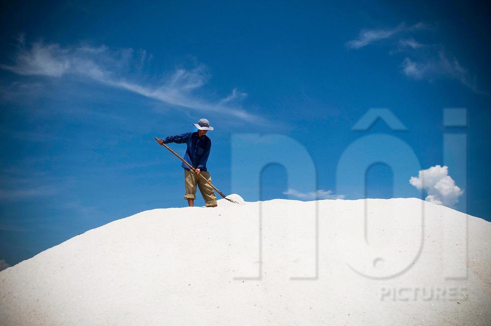 Vietnamese man works in a salt marsh of Doc Let, Khanh Hoa Province, Vietnam, Southeast Asia