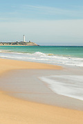 View of beach and sea with lighthouse in distance, Cadiz, Andalusia, Spain