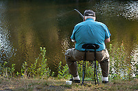 a senior man is fishing while relaxing sitting on a stool beside a beaver pond on the Kitsap Peninsula, Puget Sound, Washington, USA