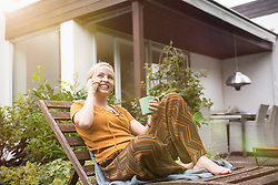 Beautiful young woman having cup of tea and talking on smartphone in the domestic garden, Munich, Bavaria, Germany