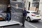 Art removal specialist workmen offload an artwork by the photographer Romina Ressia from the back of their van in Maddox Street, on 30th April 2019, in London, England.