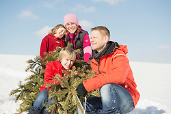 Family sitting with branches in winter, smiling, Bavaria, Germany