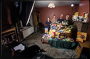 (MODEL RELEASED IMAGE). Production shot for the official family food portrait: The Bainton family in the dining area of their living room in Collingbourne Ducis, Wiltshire, with a week's worth of food. Left to right: Mark Bainton, Deb Bainton (petting Polo the dog), and sons Josh, and Tadd. (Supporting image from the project Hungry Planet: What the World Eats.)