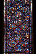Bottom corners, left shows a belt seller, right a merchant. Centre panel, bottom shows a merchant with scales, left birth of St Nicholas, left the miracles of the first bath of St Nicholas, top The infant St Nicholas refuses his mother's milk except on mondays and fridays..Medieval Windows  of the Gothic Cathedral of Chartres, France, dedicated to the life an miracles of St Nicholas. A UNESCO World Heritage Site. .Bottom centre panel,  bottom shows The young St Nicholas does well at school, left Nicholas secretly gives gold to an old man to save his daughters , right The old man tries to thank Nicholas, who humbly flees from him, top .Nicholas is chosen to be the new Bishop ..Top centre panel, bottom shows The miracle of the boiling baby, saved by the intervention of St Nicholas, left An old couple's only son falls overboard en-route to the Saint's shrine, right The child lost at sea is found safe and well at the Saint's shrine, top Installation of Nicholas as Bishop of Myra .<br /> <br /> Visit our MEDIEVAL ART PHOTO COLLECTIONS for more   photos  to download or buy as prints https://funkystock.photoshelter.com/gallery-collection/Medieval-Middle-Ages-Art-Artefacts-Antiquities-Pictures-Images-of/C0000YpKXiAHnG2k