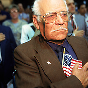 A man covers his his heart and recites the Pledge of Allegiance at a swearing-in ceremony for new citizens.