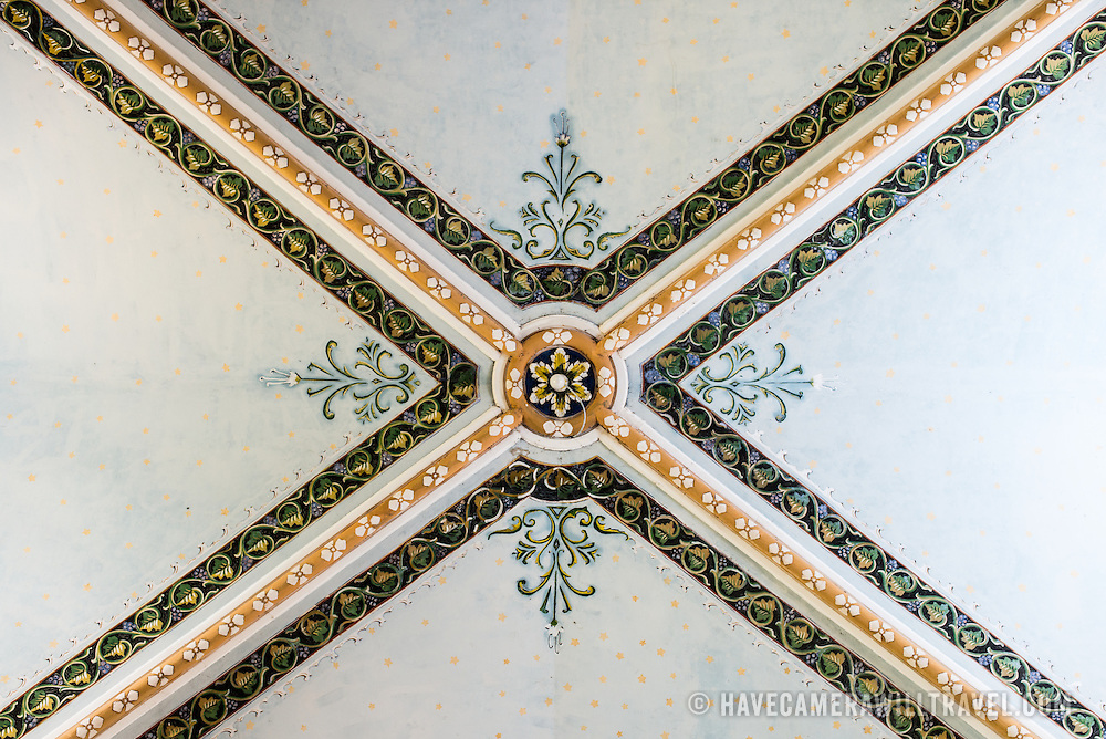 Detail of the ceiling decorations at La Capilla Maria Auxiliadora. La Capilla Maria Auxiliadora is located in the western part of Granada and features a lavishly decorated interior with walls in pastel blue and green.