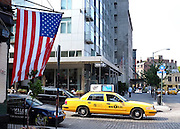 © Licensed to London News Pictures. 26/05/2012. New York, USA A yellow taxi cab passes a Stars and Stripes flag in the Meat Packing District today 26th May 2012. Photo credit : Stephen Simpson/LNP