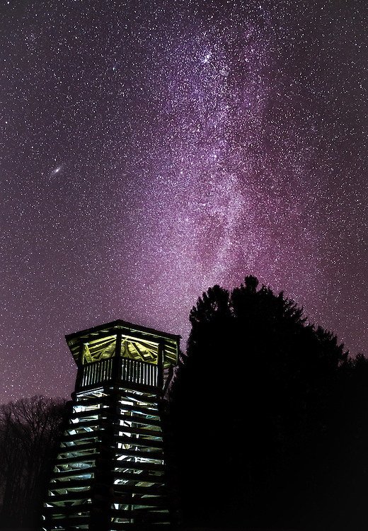 Milky way streaming over the watch tower against a silhouette of pine trees at Droop Mountain in West Virginia.