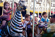 Oct 14, 2008 -- PHOENIX, AZ: People on the Merry Go Round at the Arizona State Fair. The Arizona State Fair started Oct.  10 and runs through Nov. 2. Carnival and midway workers who have worked the fair for years say attendance so far is much lower than in the past and people at the fair this year aren't spending as much money as they have in the past. Photo by Jack Kurtz / ZUMA Press