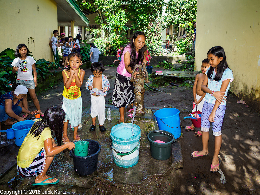 20 JANUARY 2018 - CAMALIG, ALBAY, PHILIPPINES: Evacuees forced out of their homes by the eruption of the Mayon volcano gather around a well at the Barangay Salugan evacuee shelter in a school in Camalig. There are about 870 people living at the shelter. They won't be allowed to move back to their homes until officials determine that Mayon volcano is safe and not likely to erupt. More than 30,000 people have been evacuated from communities on the near the Mayon volcano in Albay province in the Philippines. Most of the evacuees are staying at school in communities outside of the evacuation zone.  PHOTO BY JACK KURTZ