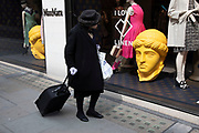 Yellow classical heads in exclusive clothes shop window for Max Mara on New Bond Street in Mayfair, London, England, United Kingdom. Bond Street is one of the principal streets in the West End shopping district and is very upmarket. It has been a fashionable shopping street since the 18th century. The rich and wealthy shop here mostly for high end fashion and jewellery.