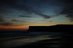 © Licensed to London News Pictures. <br /> 08/10/2014. <br /> <br /> Saltburn, United Kingdom<br /> <br /> The sun starts to rise over Huntcliff in Saltburn by the Sea in Cleveland.<br /> <br /> Photo credit : Ian Forsyth/LNP