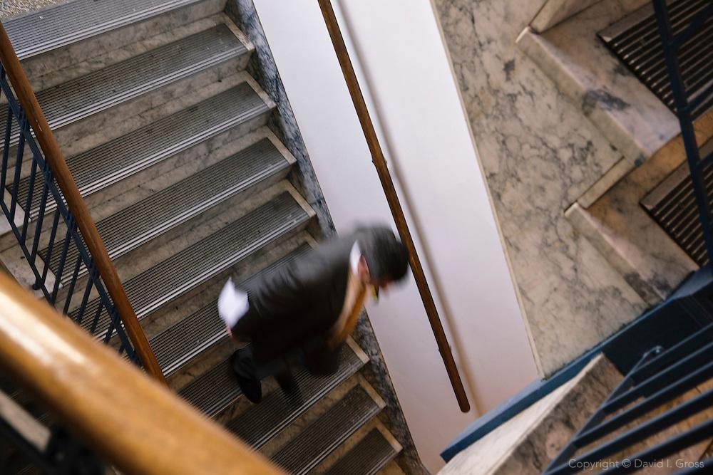 A legislator descends the  stairs at the Alaska State Legislature.